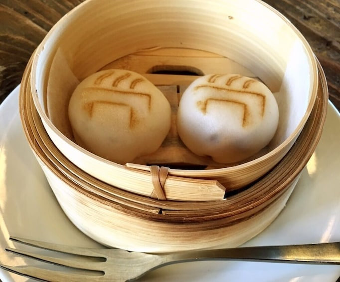Show item 4 of 10. Two pork buns in bamboo steamer