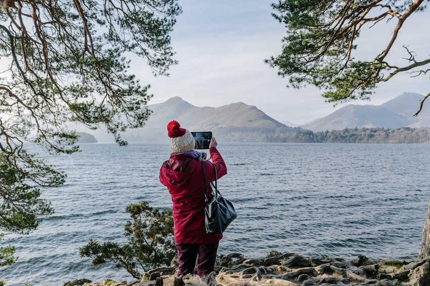 Show item 1 of 3. Tourist takes photo of Derwentwater Lake in the Lake District