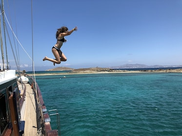 Woman jumps off of boat into water in Greece
