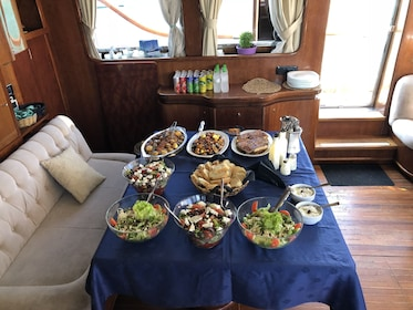 Table with salads and appetizers on boat in Greece