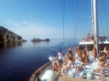 People lounge of deck as boat sails in Greece