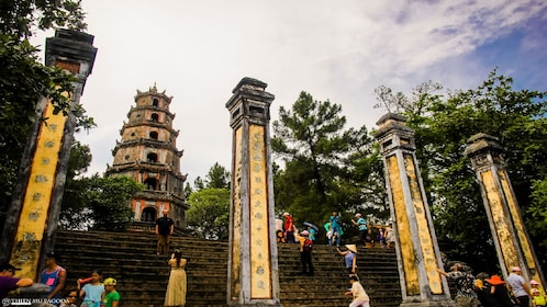 Painted columns and tourists outside of Thien Mu Pagoda