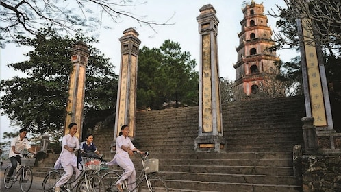 People bike past Thien Mu Pagoda in Hue, Vietnam