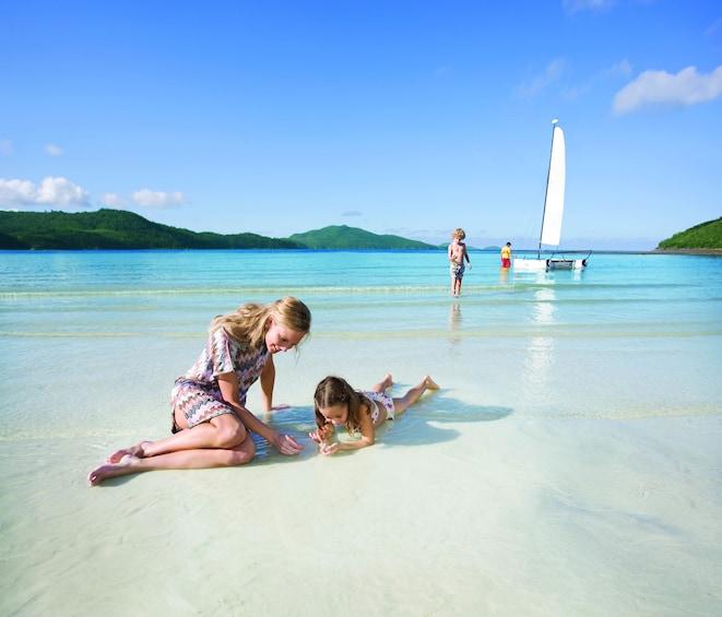 Woman and girl sit on the beach of Hamilton Island