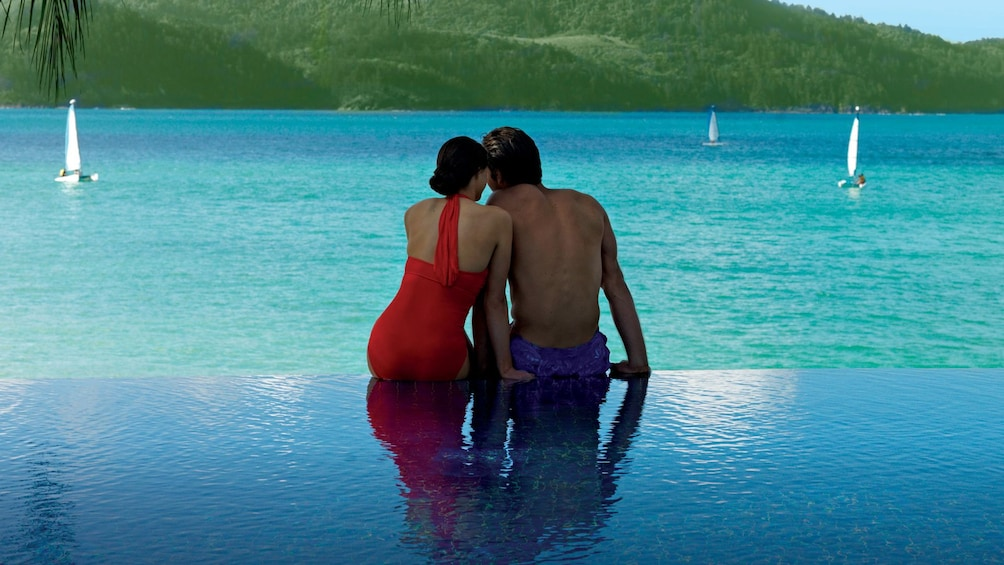 Show item 5 of 7. Couple sit together on edge of infinity pool on Hamilton Island