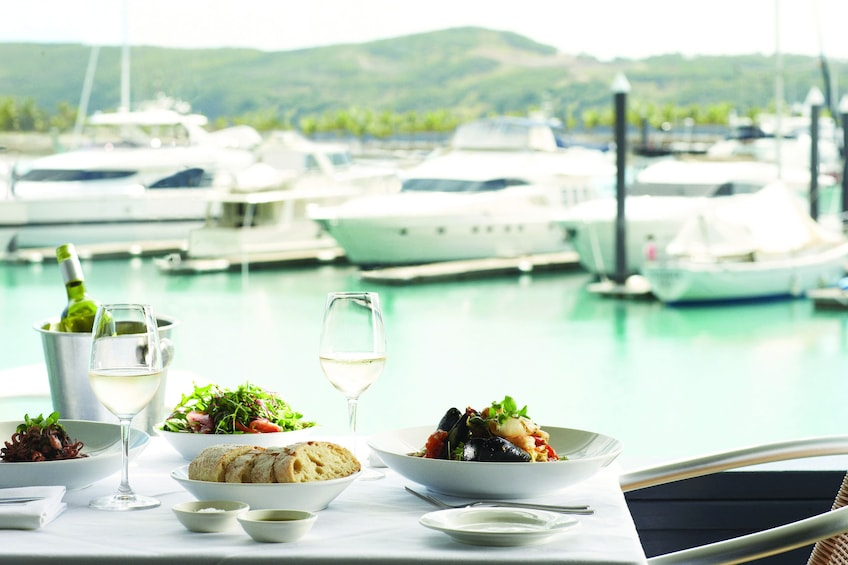 Show item 3 of 7. Table with salad and bread looking out over pier of Hamilton Island