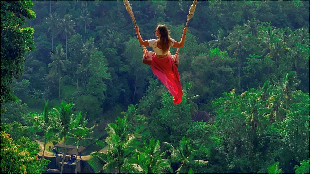 Show item 3 of 9. Woman in red dress on swing in Bali