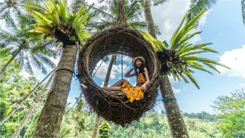 Show item 2 of 9. Woman sits in woven basket chair at Bali Swing Park