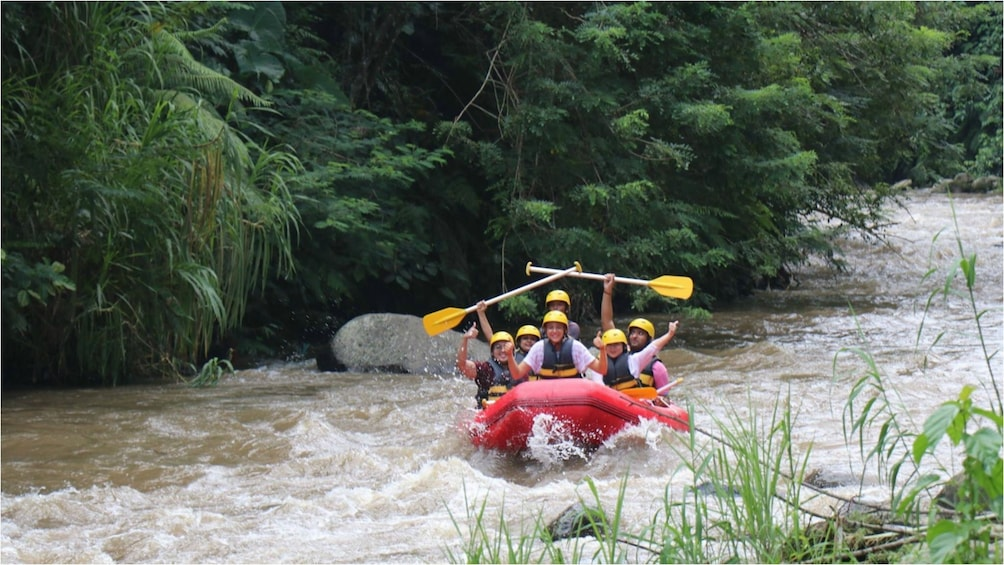 Show item 1 of 9. River rafters hold their paddles up on river in Bali