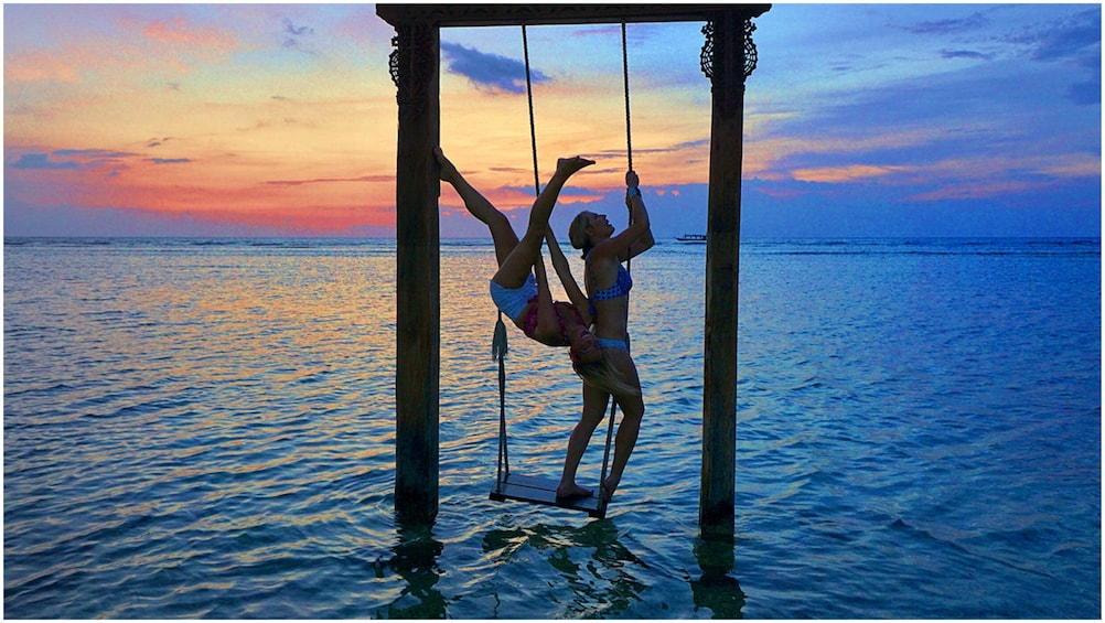 Show item 4 of 7. Two women hang on swing over water in Bali
