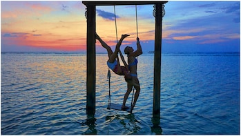 Show item 2 of 7. Two women hang on swing over water in Bali
