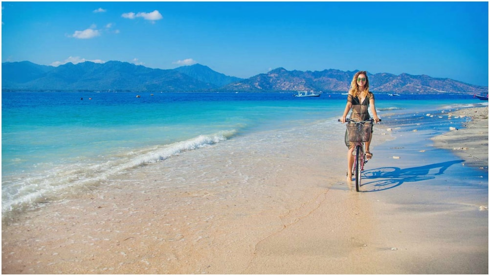 Show item 2 of 7. Woman bikes along the beach on the Gili Islands