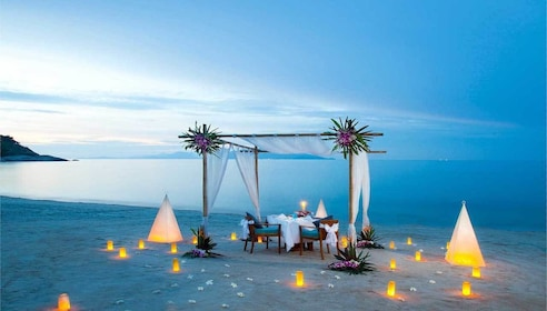Romantic dining table on the beach in Thailand at dusk