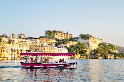 UDAIPUR, RAJASTHAN, INDIA - DECEMBER 8, 2011 Tourists on the boat taking Udaipur Lake Pichola sunset boat ride with City Palace on background.jpg