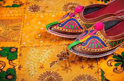 Colorful ethnic shoes on yellow Rajasthan cushion cover on flea market in India.jpg