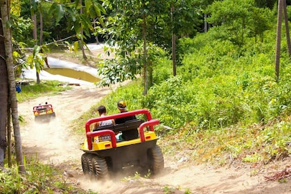 People ride down dirt path in ATVs in Koh Samui, Thailand
