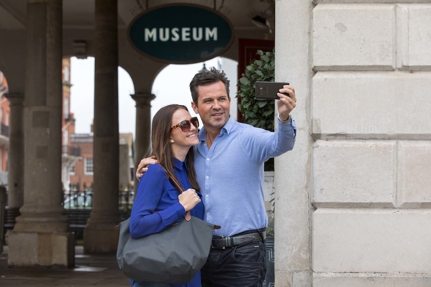 Couple taking a selfie outside the museum at the Roman Bath