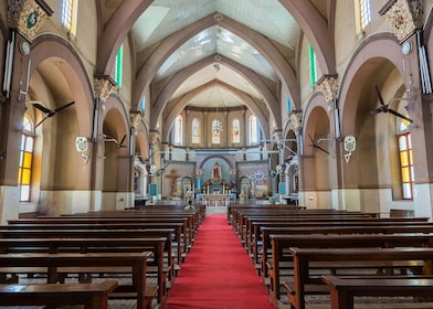 A red carpet, flanked by brown benches, leads to the altar section of this little Catholic church in Bengaluru, with the statue of the Sacred Heart.jpg