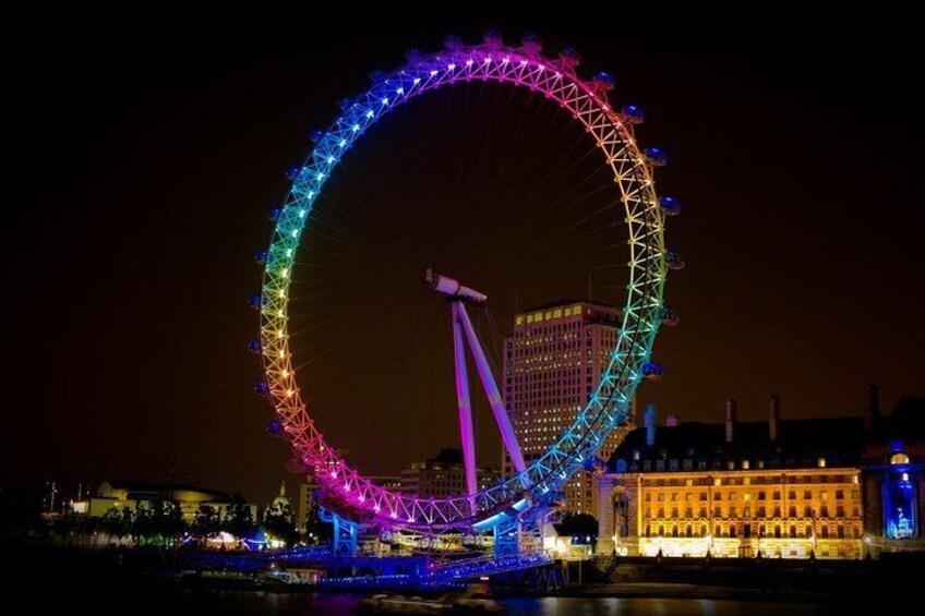 See the London Eye illuminated by night.