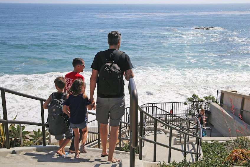 Show item 1 of 8. Family with tour guide walking down to a beach in California